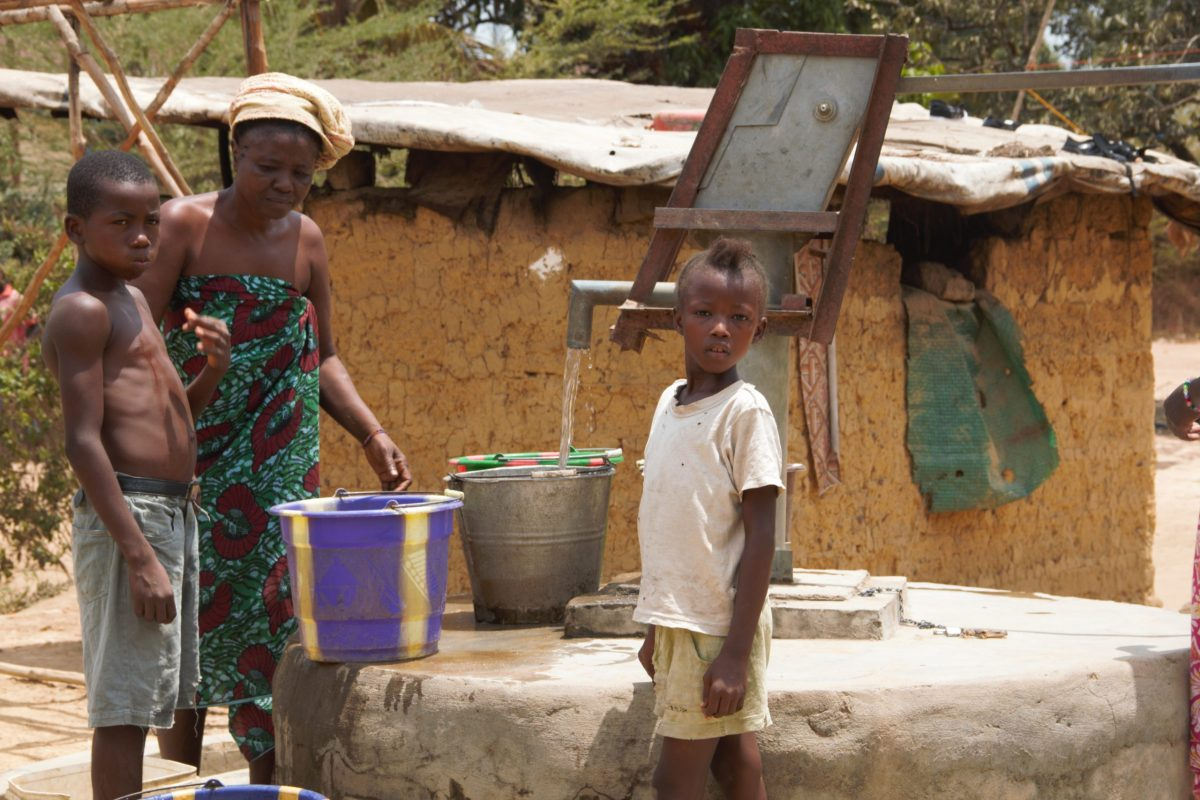 People using handpump on a hand dug well in Sierra Leone